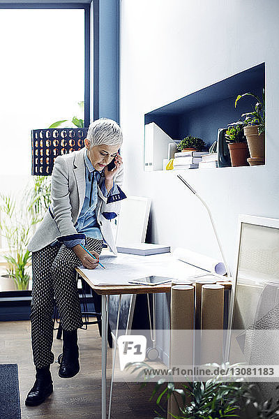Woman talking on phone while working in office