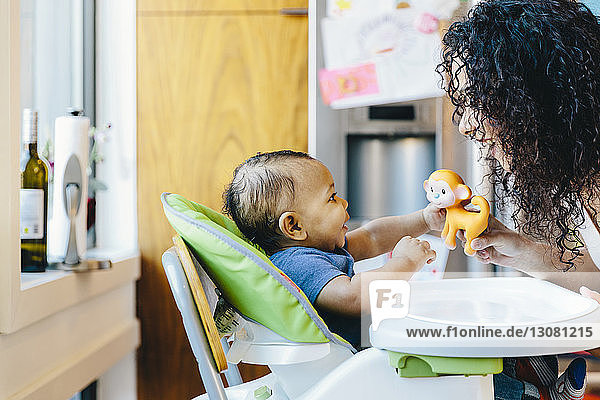 Mother playing with son sitting on high chair in kitchen at home