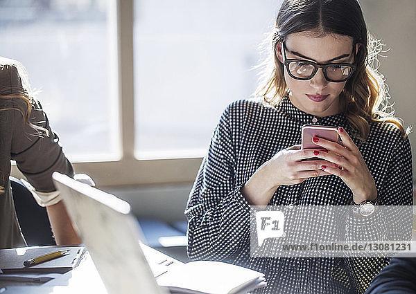 Frau benutzt Smartphone  während sie im Klassenzimmer am Tisch sitzt