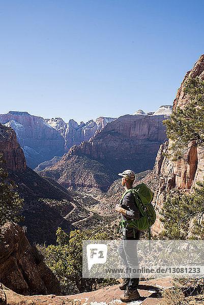 Wanderer in voller Länge mit Rucksack betrachtet Felsformationen  während er in der Wüste vor klarem Himmel steht