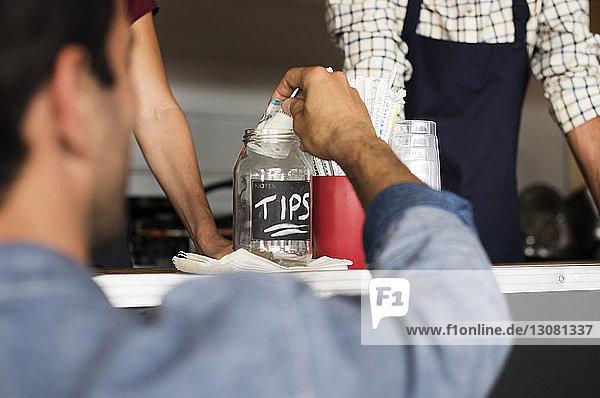Rückansicht von Kunden  die Trinkgelder in Gläser im Speisewagen mit Verkäufern geben