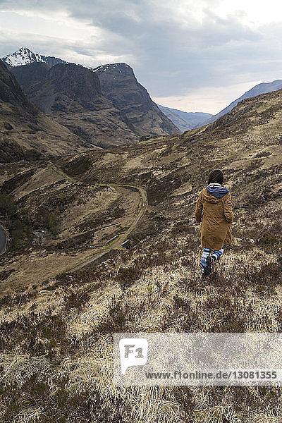 Rückansicht einer Frau  die auf einem Berg vor bewölktem Himmel geht