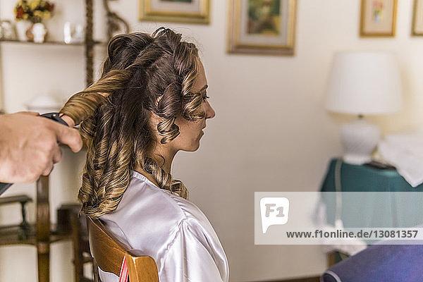Geschnittene Hände eines Friseurs  der zu Hause Lockenwickler an den Haaren der Braut benutzt
