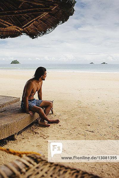 hemdloser Mann schaut weg,  während er am Strand auf dem Bett sitzt