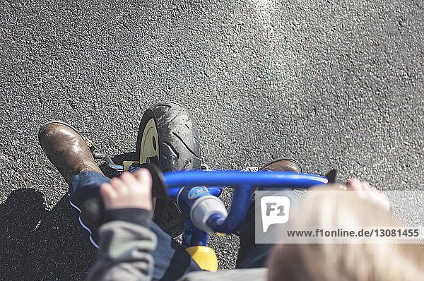 Hochwinkelaufnahme eines Jungen  der auf der Straße Fahrrad fährt