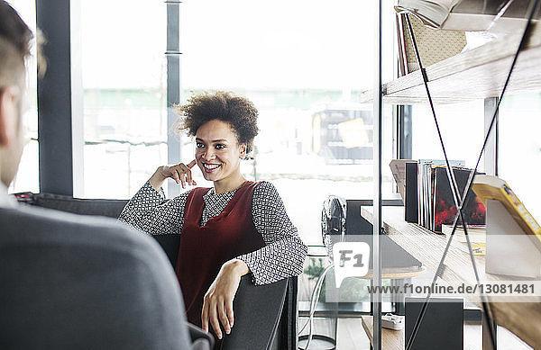Lächelnde Frau sieht Mann in hell erleuchtetem Restaurant an