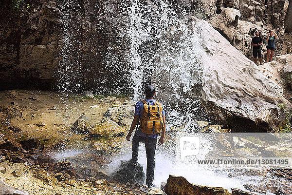 Rückansicht eines Mannes  der unter einem Wasserfall am Hängenden See steht