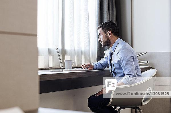 Seitenansicht eines Geschäftsmannes mit Laptop im Hotelzimmer