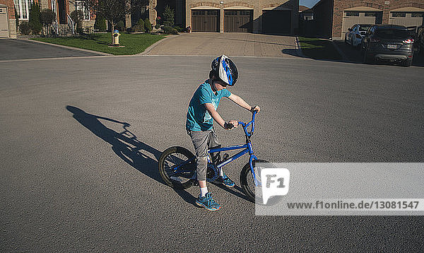 Full length of boy riding bicycle on road