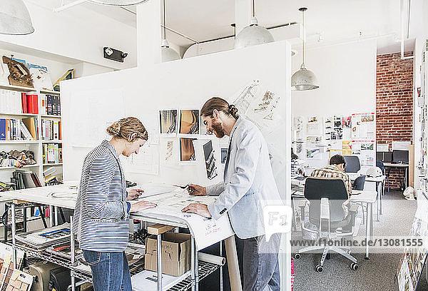 Kollegen diskutieren im Büro über Entwürfe