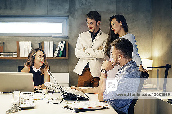 Businesswoman explaining colleagues during meeting in office