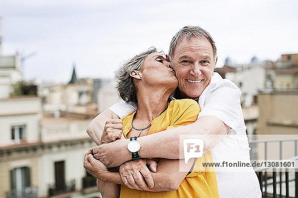 Romantische reife Frau küsst älteren Mann auf Terrasse