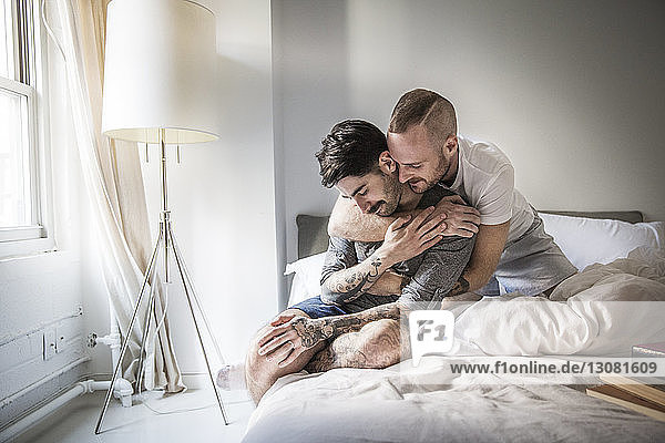 Affectionate homosexual couple on bed at home