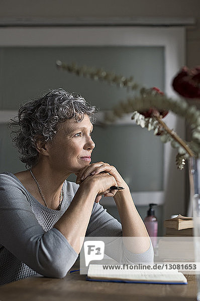 Thoughtful mature woman sitting by table at home