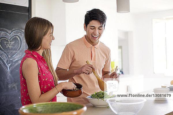 Glückliches Paar bereitet zu Hause in der Küche Salat zu