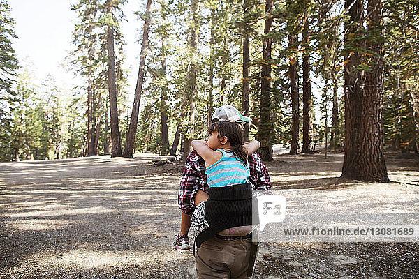 Rückansicht eines Vaters  der seine Tochter trägt und auf dem Feld gegen Bäume läuft