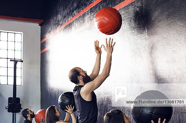 Athletes exercising with medicine balls in gym