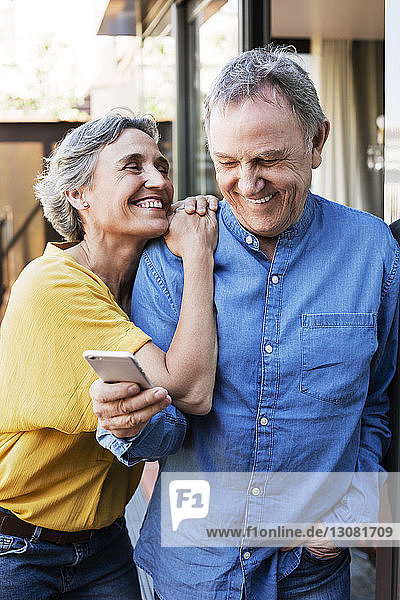 Cheerful woman looking at senior man using smart phone on porch
