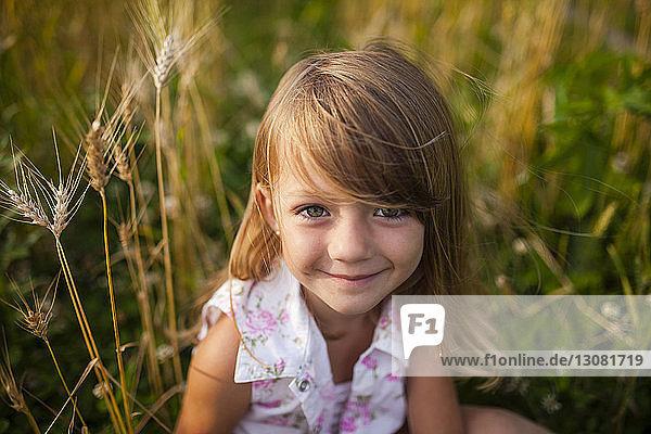 Portrait of happy girl sitting on farm