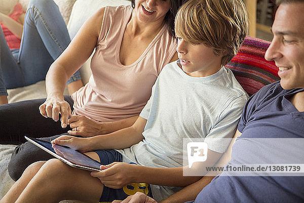Hochwinkelansicht einer Familie mit auf dem Sofa sitzendem Tablet-Computer