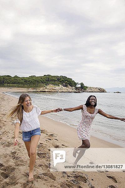 Fröhliche Freundinnen halten sich an den Händen  während sie am Strand gegen den Himmel rennen