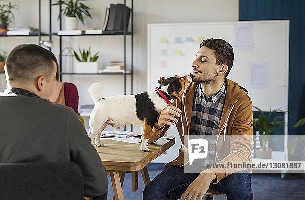 Mann spielt mit Hund  während er im Klassenzimmer am Tisch sitzt