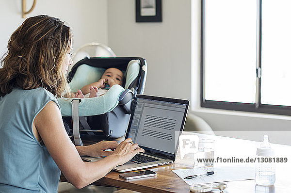 Mother using laptop computer by baby boy relaxing in seat on table at home