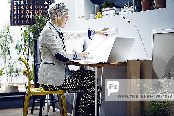Female architect analyzing blue prints at office