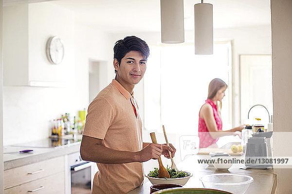 Porträt eines Salat zubereitenden Mannes mit im Hintergrund stehender Frau in der Küche
