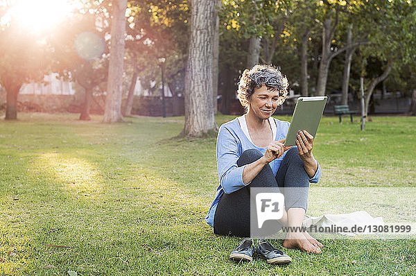 Smiling woman using digital tablet while sitting on grassy field
