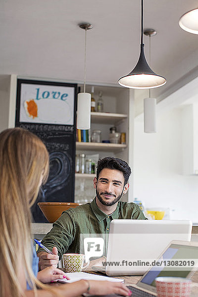 Smiling man looking at woman while using laptop at home