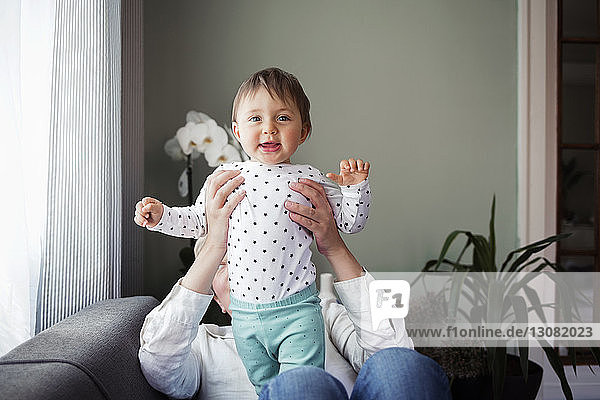 Porträt eines glücklichen kleinen Mädchens mit Großmutter  das zu Hause auf dem Sofa sitzt