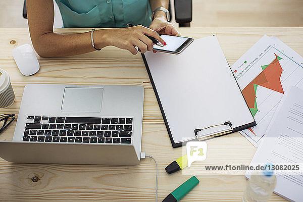 Schrägansicht einer Geschäftsfrau mit einem Smartphone am Büroschreibtisch