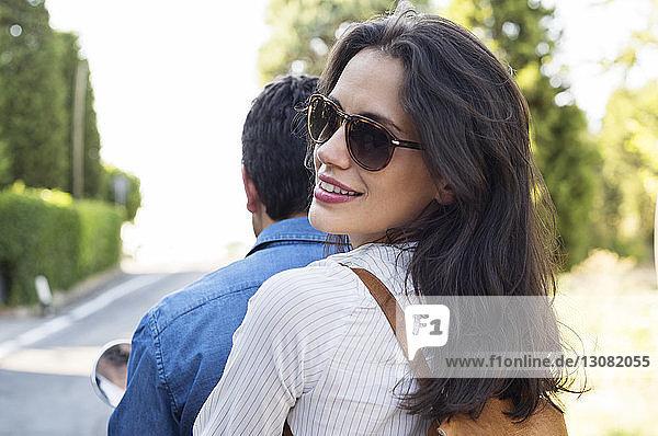 Rückansicht Porträt einer lächelnden Frau  die mit einem Mann auf einem Motorroller fährt