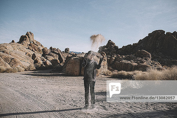 Playful boy throwing sand while standing against rock formations at desert during sunny day