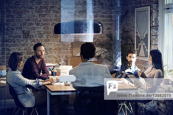 Colleagues having discussion at table in conference room