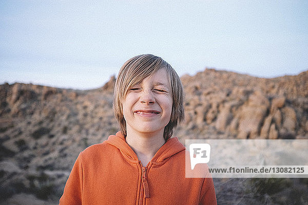 Boy with eyes closed standing at Joshua Tree National Park against clear sky during sunset