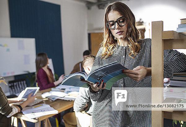 Frau liest Lehrbücher  während sie an den Regalen im Klassenzimmer steht