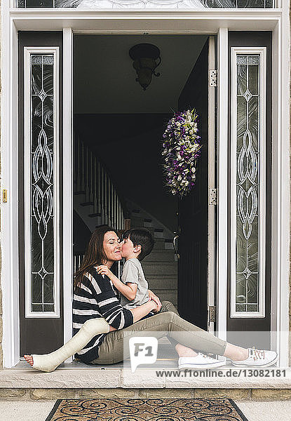 Side view of son with broken leg kissing mother while sitting on doorway at home