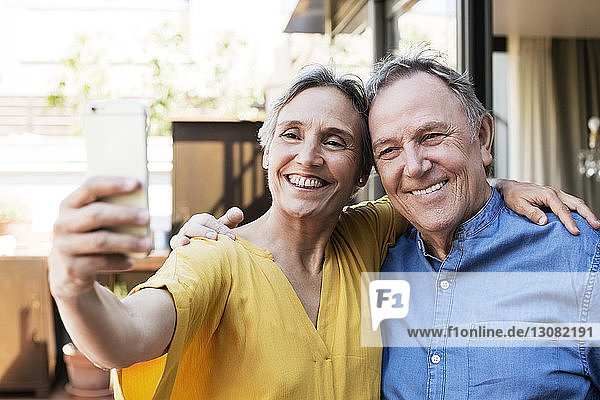 Cheerful senior couple taking selfie through smart phone at porch