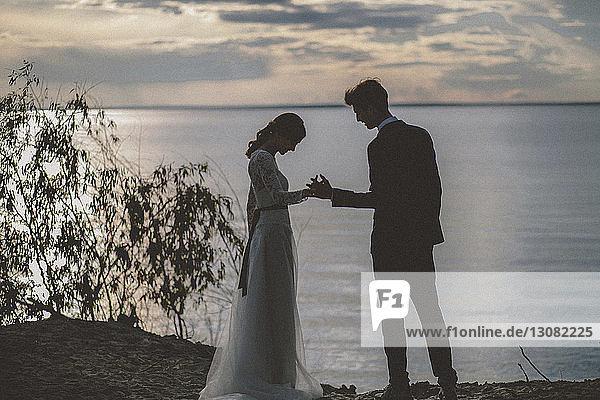 Hochzeitspaar  das bei Sonnenuntergang am Strand gegen den Himmel steht und dabei Händchen hält