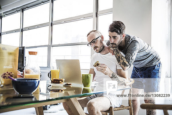 Homosexual couple looking in laptop computer while having breakfast at table
