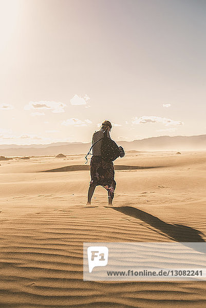 Rückansicht einer Frau mit Rucksack  die bei Sonnenuntergang auf Sand am Strand gegen den Himmel läuft