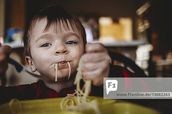 Portrait of boy eating noodles while sitting at home