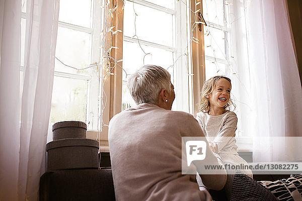 Glückliche Großmutter und Enkelin sitzen zu Hause auf dem Sofa