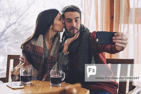 Frau küsst  während ihr Freund sich bei Tisch im Cafe mit sich selbst beschäftigt