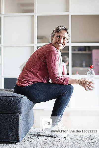 Side view portrait of happy mature woman holding water bottle while sitting on sofa at home