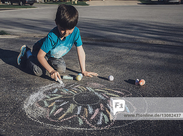 Boy drawing with chalk on asphalt