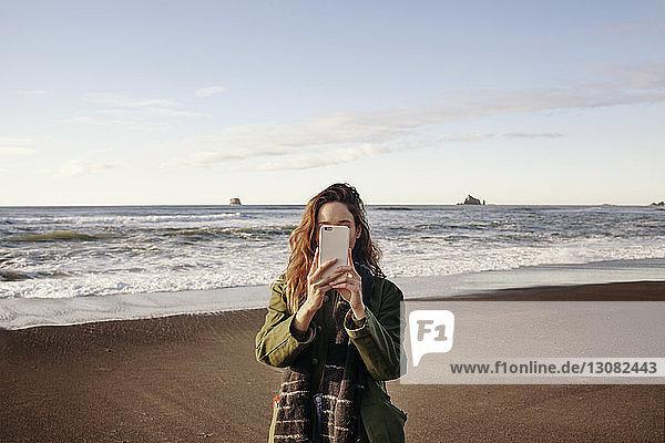 Junge Frau fotografiert mit Smartphone am Strand