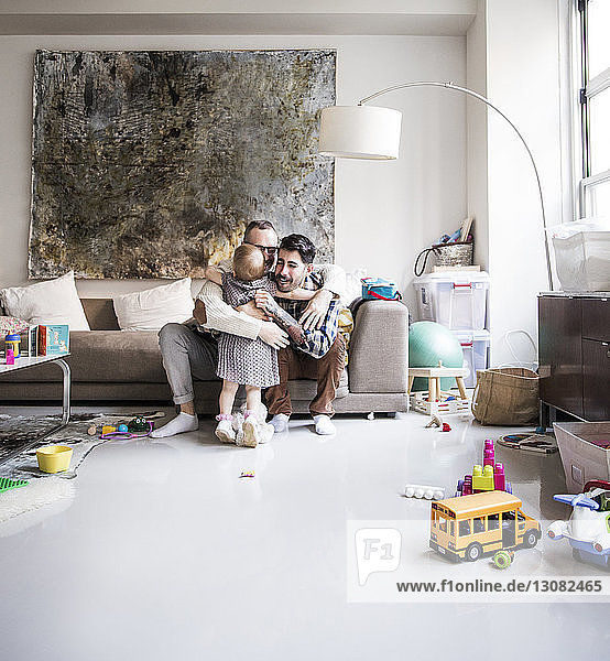 Loving fathers embracing girl while sitting in living room at home